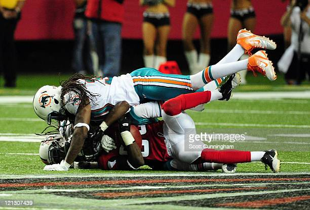 Harry Douglas of the Atlanta Falcons is tackled by Nolan Carroll and Chris Clemons of the Miami Dolphins during a preseason game at the Georgia Dome...