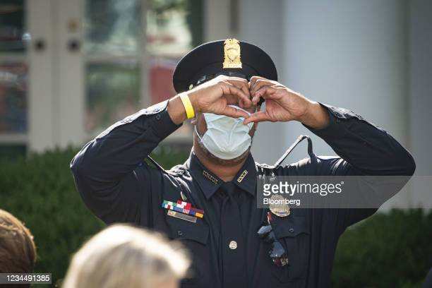 Harry Dunn, private first class with the U.S. Capitol Police, makes a heart shape with his hands as he arrives during a bill signing ceremony in the...