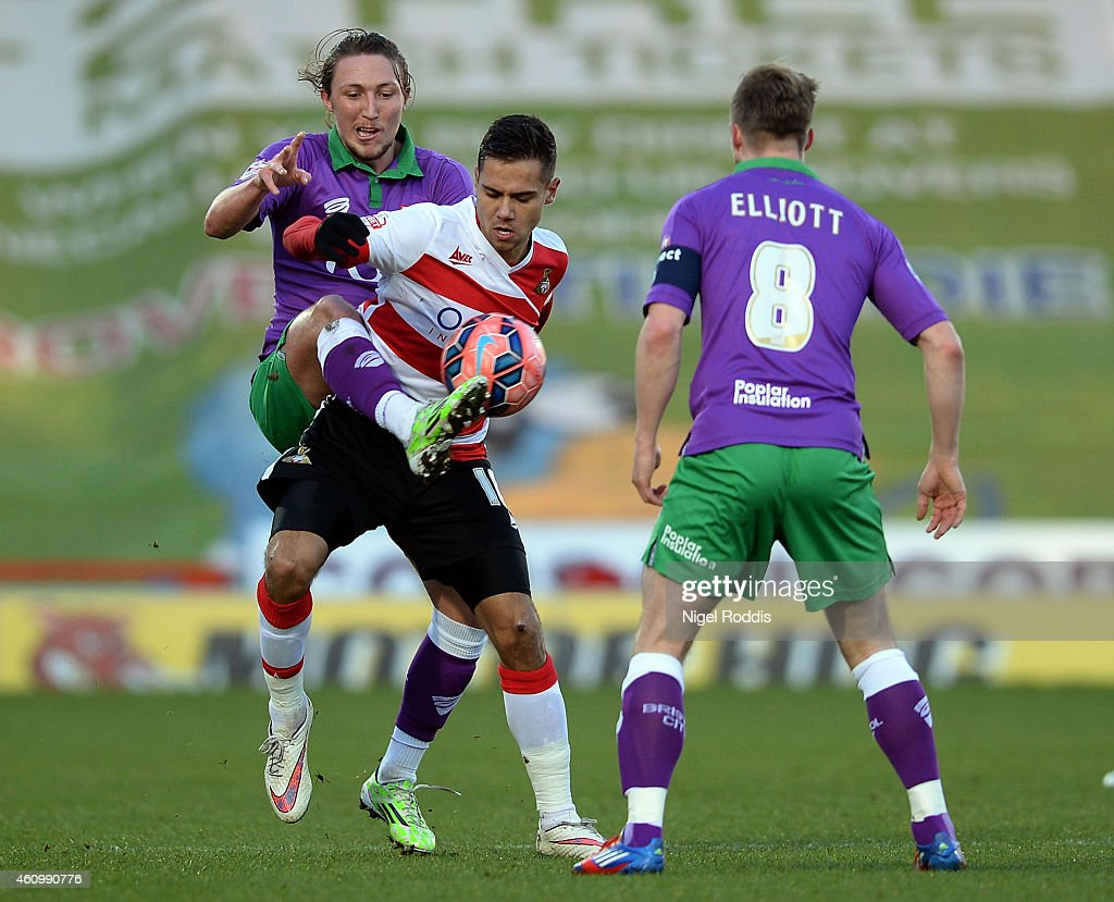 Harry Forrester (C) of Doncaster Rovers challenged by Luke Ayling (L) and Wade Elliott of Bristol City during the FA Cup Third Round match between Doncaster Rovers and Bristol City at Keepmoat Stadium on January 3, 2015 in Doncaster, England.