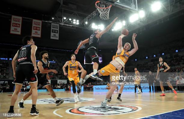 Harry Froling of the Bullets is challenged by Mason Peatling of United as he drives at the basket during the round 13 NBL match between Melbourne...
