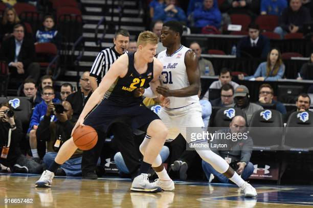 Harry Froling of the Marquette Golden Eagles dribbles around Angel Delgado of the Seton Hall Pirates during a college basketball game at the...