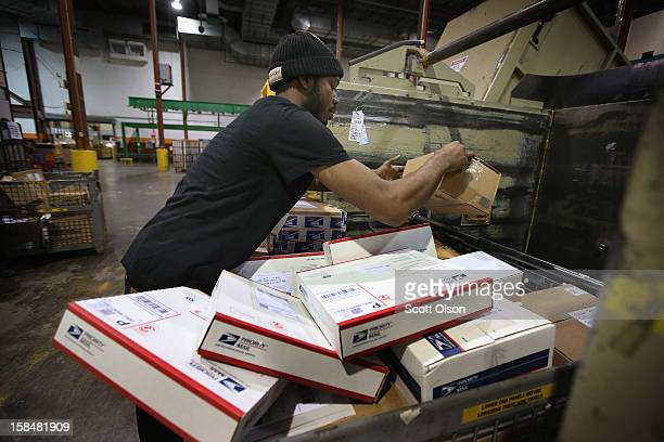 Harry Garrett loads mail onto a conveyor at the United States Postal Service Chicago Logistics and Distribution Center on December 17 2012 in Elk...