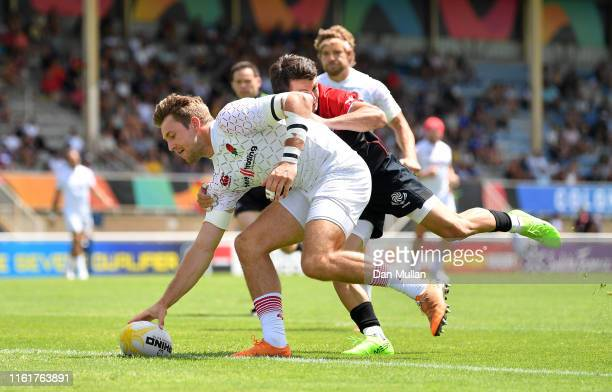 Harry Glover of England scores a try under pressure from Iago Khabuliani of Georgia during the Group C match between England and Georgia on day one...