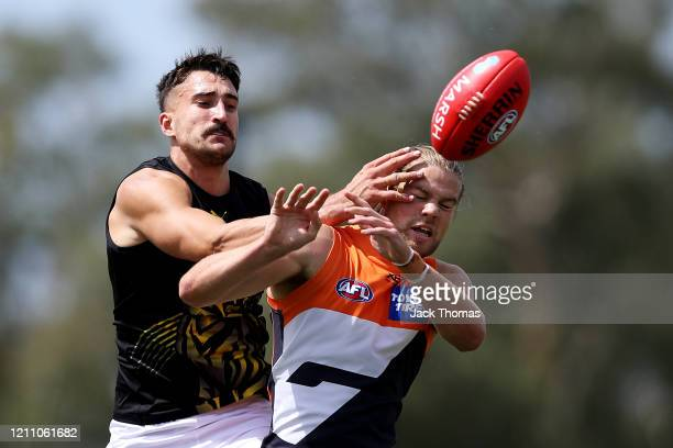 Harry Himmelberg of GWS Giants is contested by Ivan Soldo of the Richmond Tigers during the 2020 Marsh Community Series AFL match between the Greater...