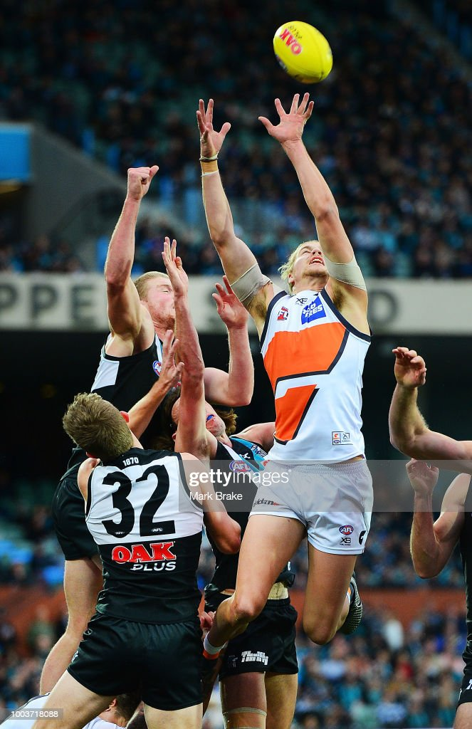 Harry Himmelberg of the Giants flys for a mark under pressure from Tom Clurey and Dougal Howard of Port Adelaide during the round 18 AFL match between the Port Adelaide Power and the Greater Western Sydney Giants at Adelaide Oval on July 22, 2018 in Adelaide, Australia.