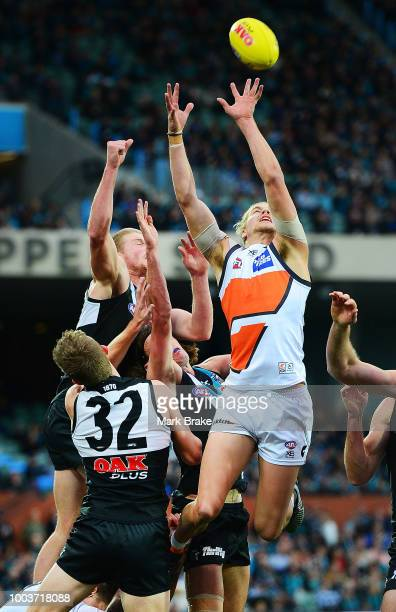 Harry Himmelberg of the Giants flys for a mark under pressure from Tom Clurey and Dougal Howard of Port Adelaide during the round 18 AFL match...