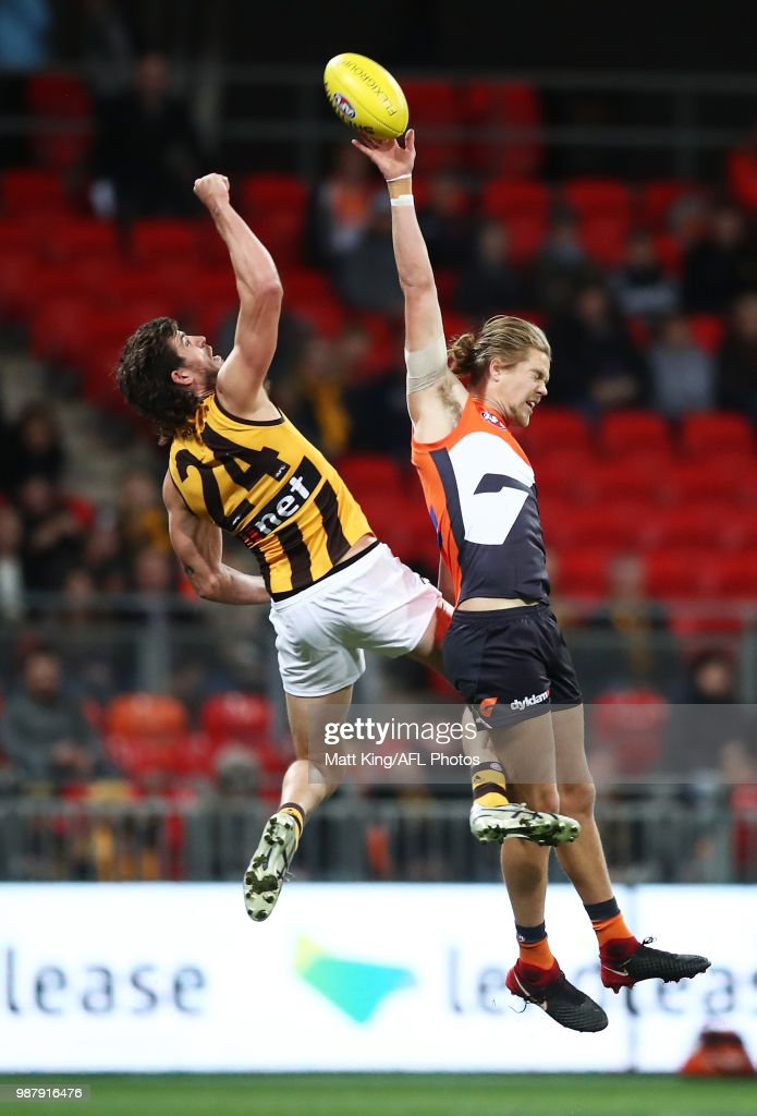 Harry Himmelberg of the Giants is challenged by Ben Stratton of the Hawks during the round 15 AFL match between the Greater Western Sydney Giants and the Hawthorn Hawks at Spotless Stadium on June 30, 2018 in Sydney, Australia.