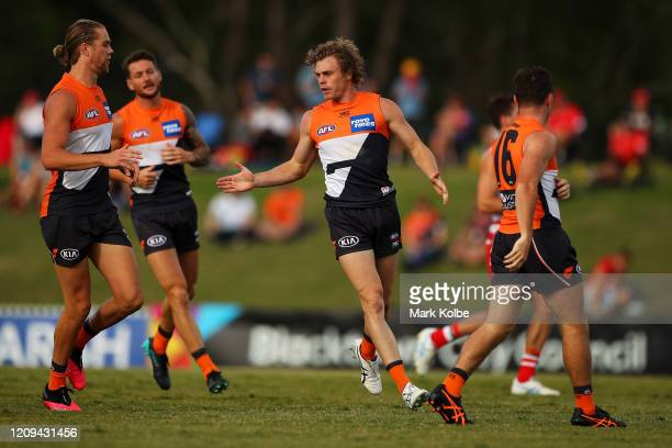 Harry Himmelbergof the Giants congratulates Adam Kennedy of the Giants after he kicked a goal during the 2020 AFL Marsh Community Series match...