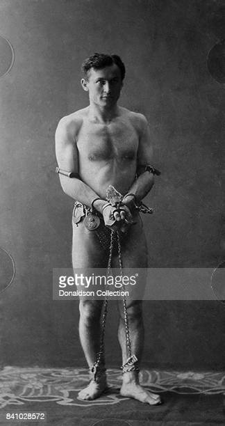 Harry Houdini fulllength portrait standing facing front in chains in circa 1900