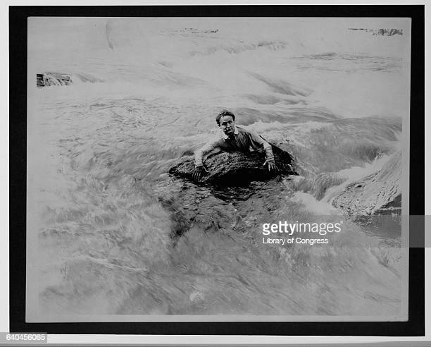 Harry Houdini grasping a rock in fastmoving rapids in a scene from a movie