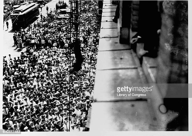 Harry Houdini hangs suspended upsidedown over a street in a straightjacket one of his most famous escape stunts A crowd has gathered beneath him