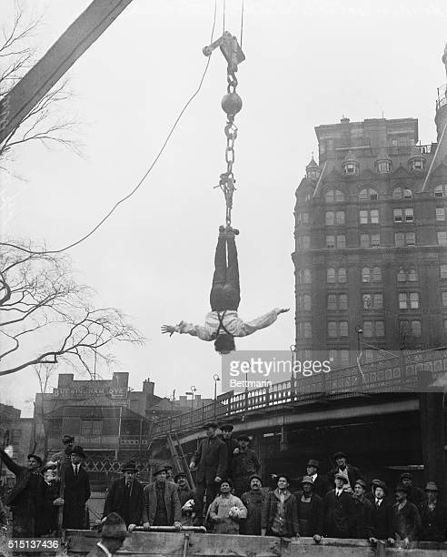 Harry Houdini hangs upside down from a crane after freeing himself from a straitjacket