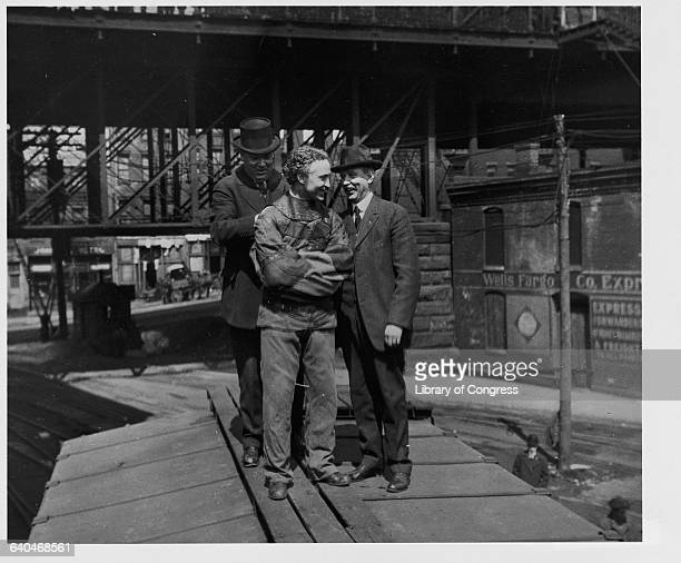 Harry Houdini is strapped into a straitjacket as he prepares for a stunt on top of a railroad car