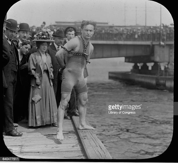 Harry Houdini stands in chains at the edge of a pier ready to dive into the water