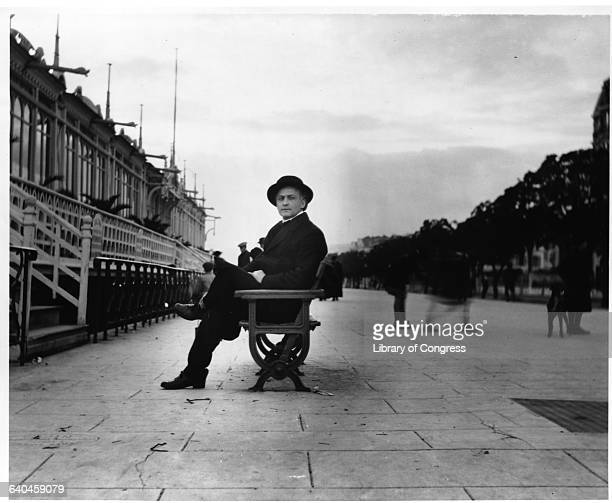 Harry Houdini the famous escape artist relaxes on a bench at Nice