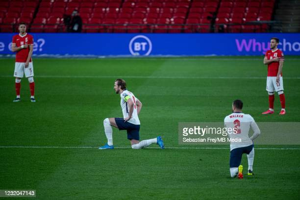 Harry Kane and Kyle Walker of England take a knee while Jan Bednarek, Maciej Rybus of Poland point point UEFA No racism logo during the FIFA World...