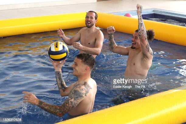 Harry Kane, Kalvin Phillips and Kieran Trippier of England react during a game of volley ball in the swimming pool at St George's Park on June 30,...