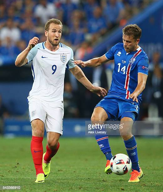 Harry Kane of England and Kari Arnason of Iceland compete for the ball during the UEFA EURO 2016 round of 16 match between England and Iceland at...