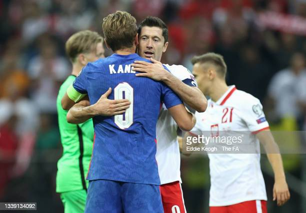 Harry Kane of England and Robert Lewandowski of Poland embrace following the 2022 FIFA World Cup Qualifier match between Poland and England at...
