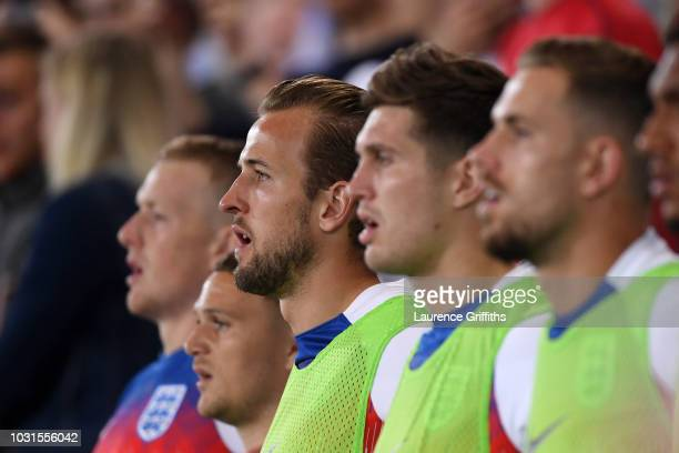 Harry Kane of England and team mates sing the national anthem prior to the international friendly match between England and Switzerland at The King...