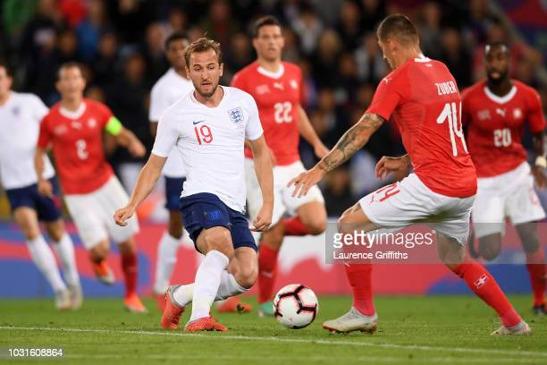 Harry Kane of England battles with Steven Zuber of Switzerland during the international friendly match between England and Switzerland at The King...