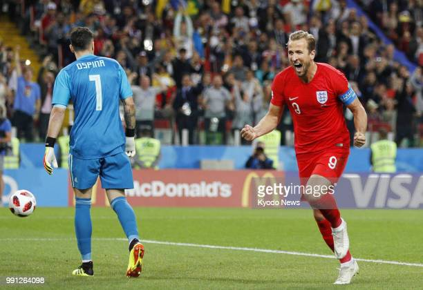 Harry Kane of England celebrates next to Colombia goalkeeper David Ospina after scoring the opening goal from the penalty spot during the second half...