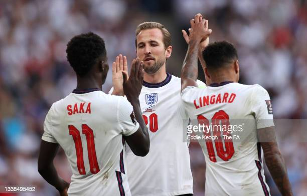Harry Kane of England celebrates with Bukayo Saka and Jesse Lingard after scoring their team's second goal from the penalty spot during the 2022 FIFA...