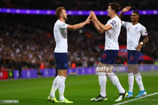 Harry Kane of England celebrates with Harry Maguire and Marcus Rashford after scoring a goal to make it 20 during the UEFA Euro 2020 qualifier match...