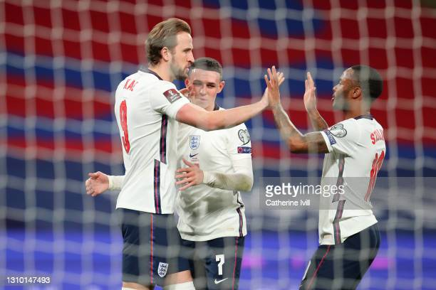Harry Kane of England celebrates with Phil Foden and Raheem Sterling after scoring their side's first goal from the penalty spot during the FIFA...