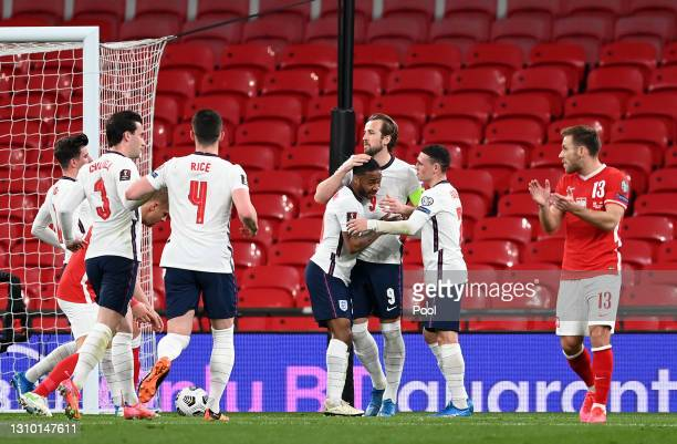 Harry Kane of England celebrates with Raheem Sterling and Phil Foden after scoring their side's first goal from the penalty spot during the FIFA...