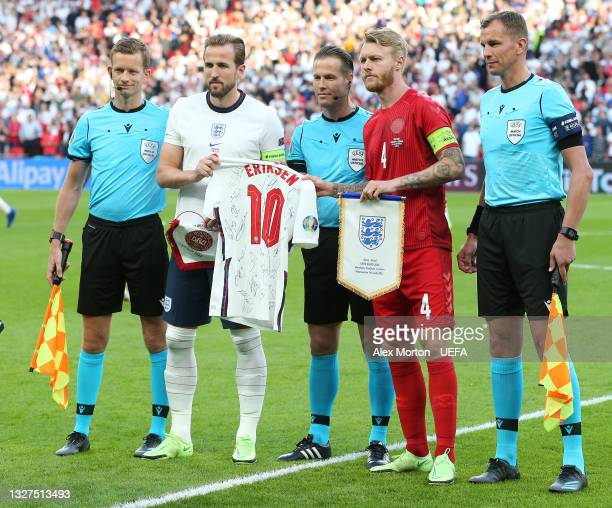 Harry Kane of England presents a signed Christian Eriksen England shirt to Simon Kjaer of Denmark as they pose for a photo with the Match Officials...