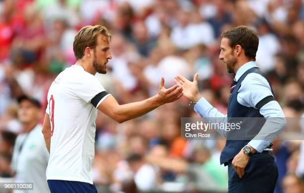 Harry Kane of England shakes hands with Gareth Southgate Manager of England after being substituted during the International Friendly match between...