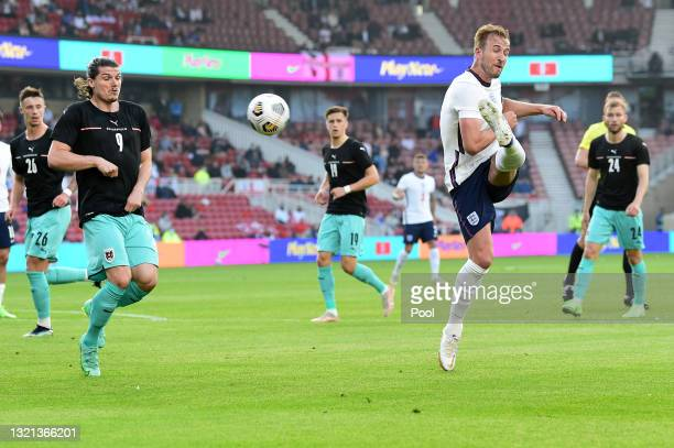 Harry Kane of England shoots and misses whilst under pressure from Marcel Sabitzer of Austria during the international friendly match between England...