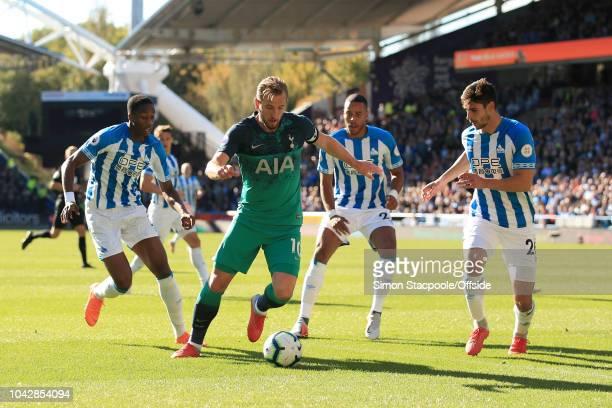 Harry Kane of Spurs battles with Terence Kongolo of Huddersfield , Mathias Zanka Jorgensen of Huddersfield and Christopher Schindler of Huddersfield...