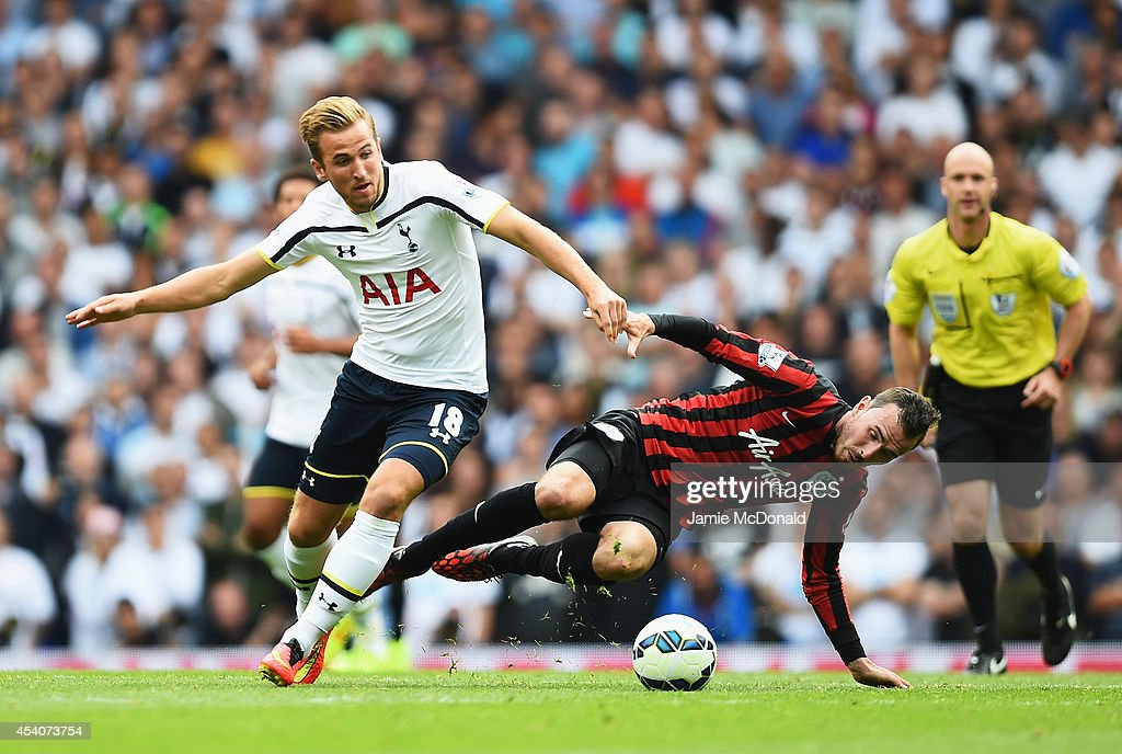 Harry Kane of Spurs is challenged by Jordon Mutch of QPR during the Barclays Premier League match between Tottenham Hotspur and Queens Park Rangers at White Hart Lane on August 24, 2014 in London, England.