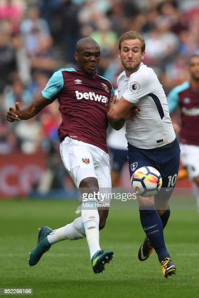 Harry Kane of Tottenham battles with Angelo Ogbonna of West Ham during the Premier League match between West Ham United and Tottenham Hotspur at...