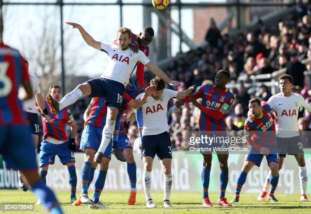 Harry Kane of Tottenham falls across Ben Davies of Tottenham and Aaron WanBissaka after going up for a header with Christian Benteke of Crystal...