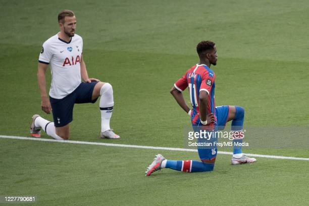 Harry Kane of Tottenham Hotspur and Wilfried Zaha of Crystal Palace take a knee during the Premier League match between Crystal Palace and Tottenham...