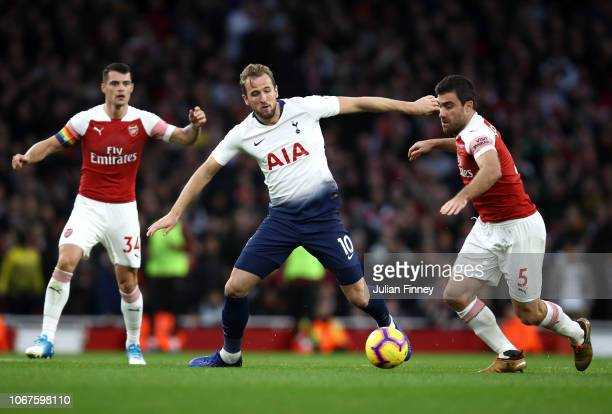 Harry Kane of Tottenham Hotspur battles for possession with Sokratis Papastathopoulos of Arsenal during the Premier League match between Arsenal FC...