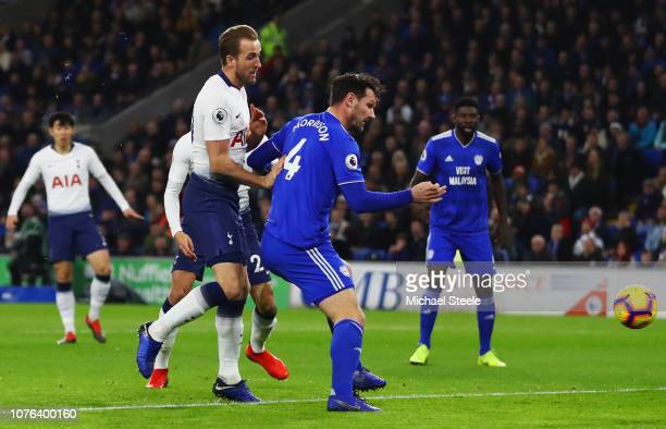 Harry Kane of Tottenham Hotspur beats Sean Morrison of Cardiff City as he scores his team's first goal during the Premier League match between...