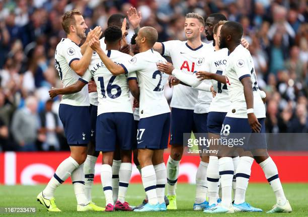 Harry Kane of Tottenham Hotspur celebrates with teammates after scoring his team's third goal during the Premier League match between Tottenham...
