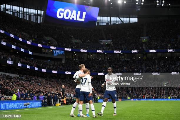 Harry Kane of Tottenham Hotspur celebrates with teammates after scoring his team's first goal during the Premier League match between Tottenham...