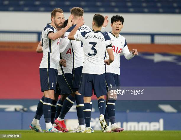 Harry Kane of Tottenham Hotspur celebrates with teammates after scoring their team's first goal during the Premier League match between Everton and...
