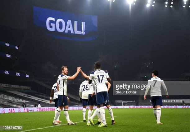 Harry Kane of Tottenham Hotspur celebrates with teammates Harry Winks and Moussa Sissoko after scoring their team's first goal during the Premier...