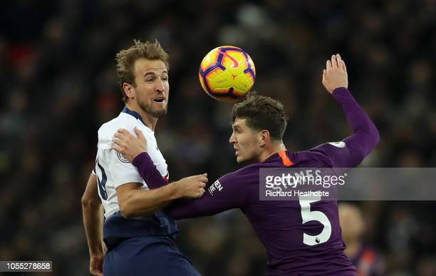 Harry Kane of Tottenham Hotspur challenges for the ball with John Stones of Manchester City during the Premier League match between Tottenham Hotspur...