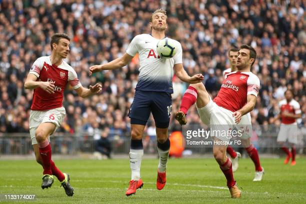 Harry Kane of Tottenham Hotspur controls the ball as he is closed down by Sokratis Papastathopoulos and Laurent Koscielny of Arsenal during the...