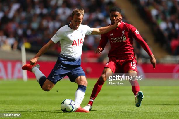 Harry Kane of Tottenham Hotspur crosses while under pressure from Joe Gomez of Liverpool during the Premier League match between Tottenham Hotspur...