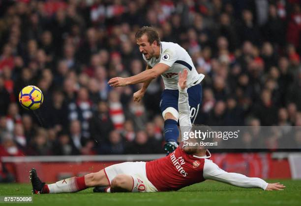 Harry Kane of Tottenham Hotspur fires in a shot as Shkodran Mustafi of Arsenal challenges during the Premier League match between Arsenal and...