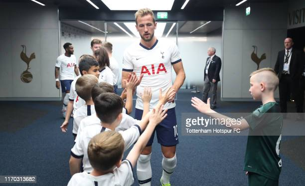 Harry Kane of Tottenham Hotspur greets the mascots during the Premier League match between Tottenham Hotspur and Newcastle United at Tottenham...
