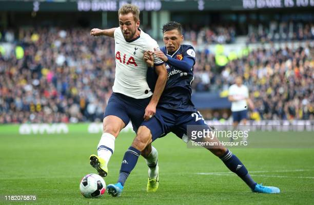 Harry Kane of Tottenham Hotspur is challenged by Jose Holebas of Watford during the Premier League match between Tottenham Hotspur and Watford FC at...